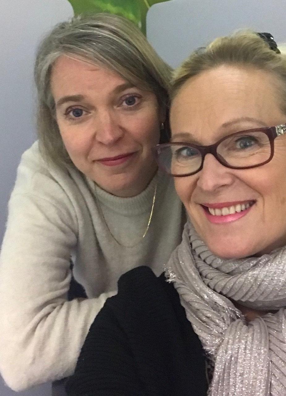 Anu Toija ja Tarja Nordman katsovat kameraan ja hymyilevät. Anu nojaa Tarjan olkapäähän.
