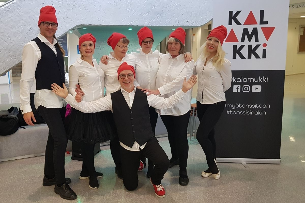 Kalamukki -tanssiryhmä Ilonan-päivä esityksensä jälkeen. Esiintyjillä on tonttulakit päässään, muuten asu on mustavalkoinen. Kaikki hymyilevät iloisesti.
