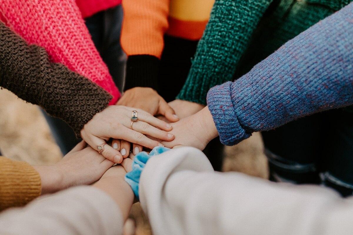 Ringissä seisovat ihmiset ovat asettaneet kätensä päällekkäin.