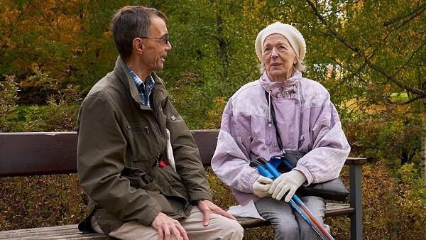 Kaksi ihmistä keskustelevat penkillä syksyisessä maisemassa. Toisella heistä on kävelysauvat mukana.