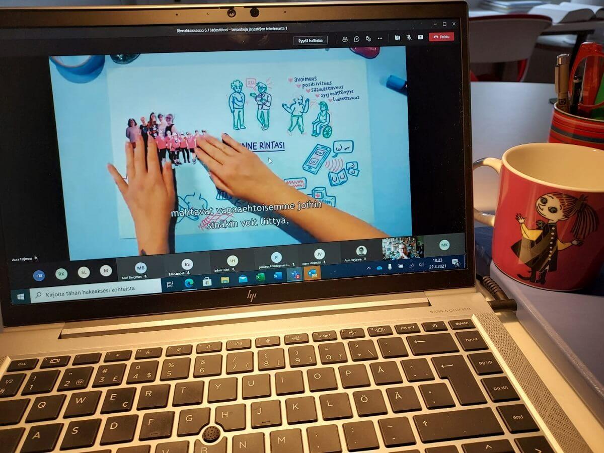 Pöydällä on Muumi-aiheinen kahvimuki sekä läppäri, jolla meneillään Teams-kokous.