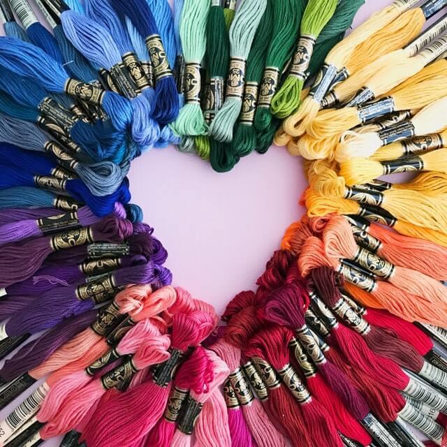 Eriväriset värikkäät lankaniput on asetettu niin, että keskelle muodostuu sydämenmuotoinen aukko.