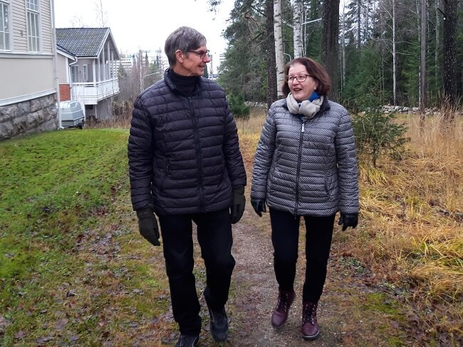 Kainuun Aivoyhdistyksen Marja Hirvonen ja hänen puolisonsa kävelevät metsäisellä polulla syksyisessä säässä.
