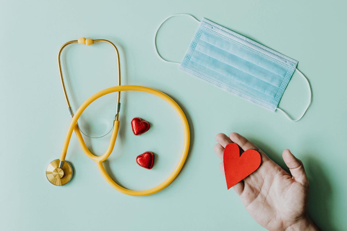 Tasolla on stetoskooppi, kasvomaski ja sydänkuvioita. Tason ylle ojennettu käsi pitelee paperisydäntä.