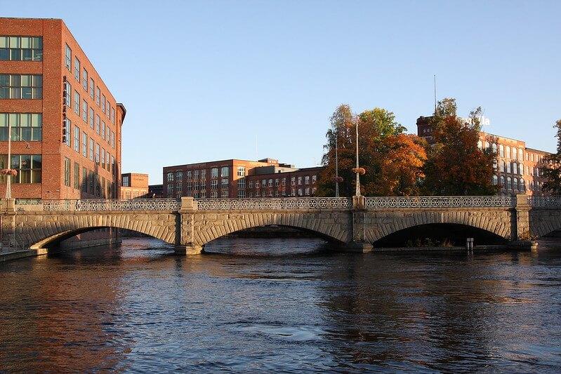 Näkymä Tampereen Tammerkoskelle. Keskellä on silta yli kosken, ympärillä punatiilisiä rakennuksia.