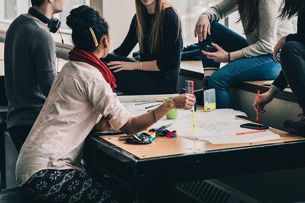 Pöydän ääressä on pieni joukko ihmisiä, jotka keskustelevat keskenään. Pöydällä on iso valkoinen paperi, johon on kirjoitettu ja piirretty. Ihmisillä on käsissään erivärisiä kyniä.